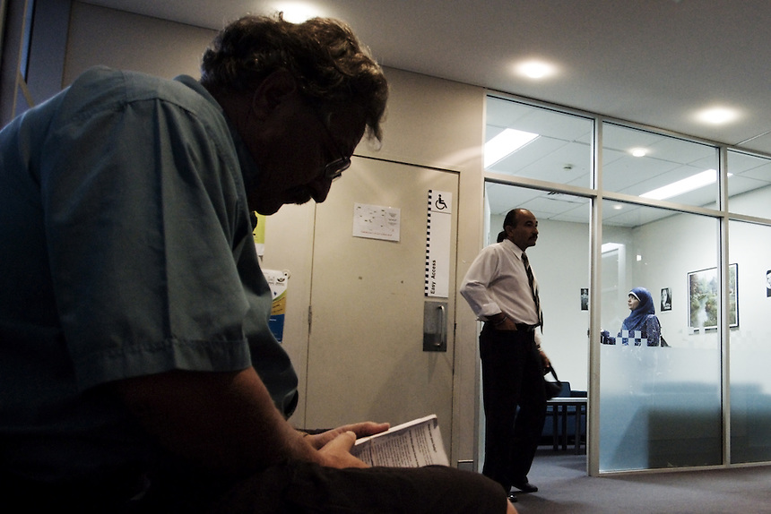 Campaign manager Raul Bassi sits reading a book at Auburn Police station, as Mamdouh and Maha Habib make statements regarding a man who accosted the group during a street campaign in central Auburn, western Sydney, March 2007.