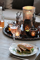 Ornamental reindeer eye up a home-made sandwich on the coffee table, made with chicken breast, bacon, rocket, aioli, pesto, tomato and red onion served on foccacia bread