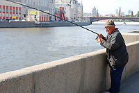 Old fisherman catching fish in Moscow downtown on Moskva river with Kremlin skyline on bavkground