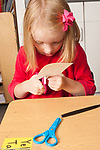 Education Elementary Kindergarten closeup of female student cutting paper with scissors
