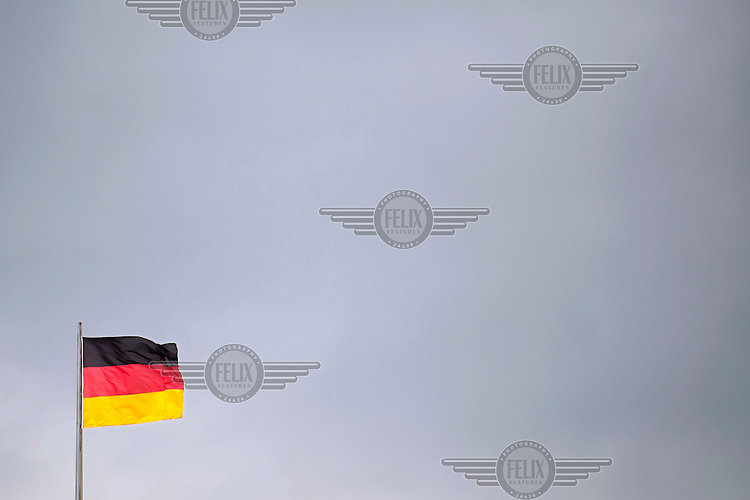 A German flag flies from the top of the German Parliament building.