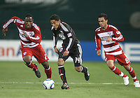 Andy Najar #14 of D.C. United breaks away from Edson Edwards #27 and Bruno Guarda #8 of F.C. Dallas during a US Open Cup match on April 28 2010, at RFK Stadium in Washington D.C. D.C. United won 4-2.