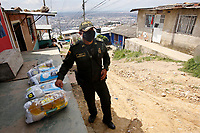 SOACHA, COLOMBIA - APRIL 15: A police officer stand guard as members of the local government workers deliver food to the community during the mandatory preventive quarantine to prevent the spread of the new coronavirus in Soacha Colombia on April 15, 2020. Soacha's mayor visited the slums of the town handing out baskets of food to help families in difficult financial times due to Covid-19 pandemic. (Photo by Leonardo Munoz/VIEWpress via Getty Images)