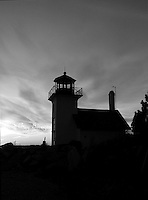 A black and white silhouette of the Bristol Ferry Lighthouse at sunset.