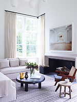 The family room's custom sofa is upholstered in a Rogers & Goffigon linen; the cocktail table is by Charlotte Perriand, the armchair is by Pierre Jeanneret, and the stool is by Christian Astuguevieille; the rug is from FJ Hakimian, and the artwork is by Sam Taylor-Johnson.