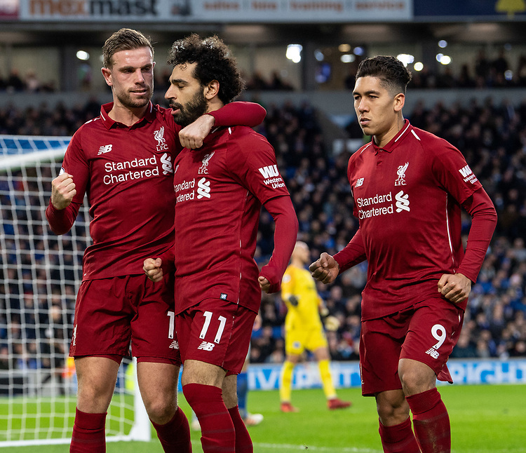 Liverpool's Mohamed Salah (center) celebrates scoring the opening goal (penalty) with team members Liverpool's Jordan Henderson (left) and Roberto Firmino (right) <br /> <br /> Photographer David Horton/CameraSport<br /> <br /> The Premier League - Brighton and Hove Albion v Liverpool - Saturday 12th January 2019 - The Amex Stadium - Brighton<br /> <br /> World Copyright © 2018 CameraSport. All rights reserved. 43 Linden Ave. Countesthorpe. Leicester. England. LE8 5PG - Tel: +44 (0) 116 277 4147 - admin@camerasport.com - www.camerasport.com
