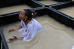 An Eritrean asylum-seeker, living in Israel, baptizes in a tank filled with water from Jordan River, during the Feast of the Epiphany, at the baptismal site of Qasr el Yahud on the Jordan River western bank. The spot is believed to be  where John the Baptist baptized Jesus, near the West Bank town of Jericho.