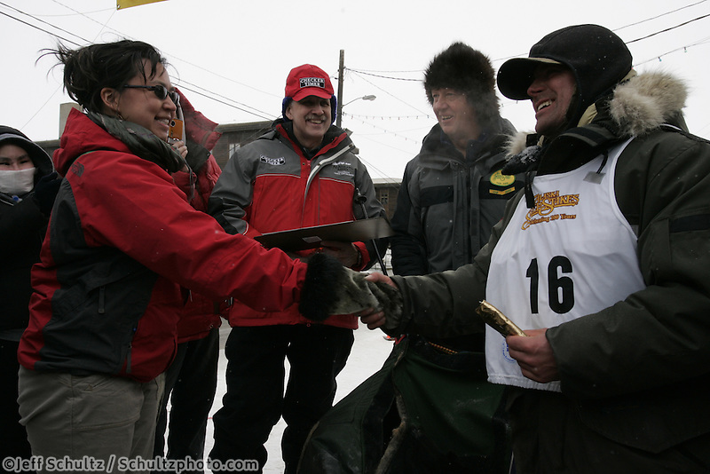 Cim Smyth crosses the finish line on Front Street  in 7th   place in the  2008 All Alaska Sweepstakes Sled Dog Race, Alaska.