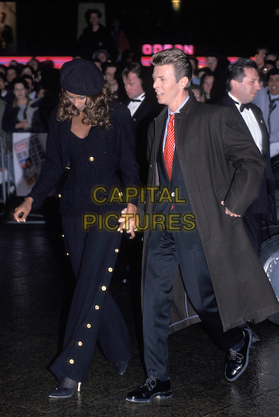 IMAN & DAVID BOWIE.Leicester Square, .London, 9 April 1995.full length black suit overcoat red white polka dot tie gold button sailor trousers jacket beret hat holding hands couple husband wife.www.capitalpictures.com.sales@capitalpictures.com.©Capital Pictures