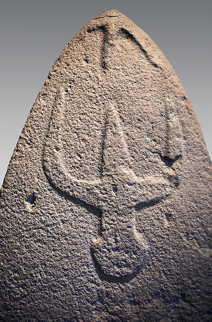 Late European Neolithic prehistoric Menhir standing stone with carvings on its face side. The representation of a stylalised male figure starts at the top with a long nose from which 2 eyebrows arch around the top of the stone. below this is a carving of a falling figure with head at the bottom and 2 curved arms encircling a body above. Excavated from Genna Arrele II. Menhir Museum, Museo della Statuaria Prehistorica in Sardegna, Museum of Prehoistoric Sardinian Statues, Palazzo Aymerich, Laconi, Sardinia, Italy. Grey background.
