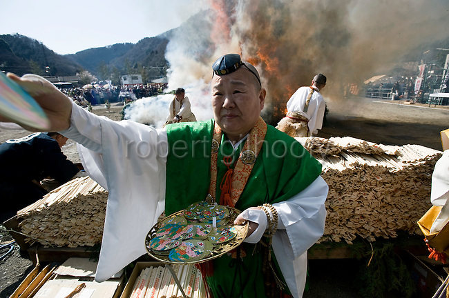 A priest from the Shingon sect of Buddhism throws out good luck cards during a purification ritual in which participants walk barefoot across burning embers in Takao, west of Tokyo, Japan on 14 March 2010.