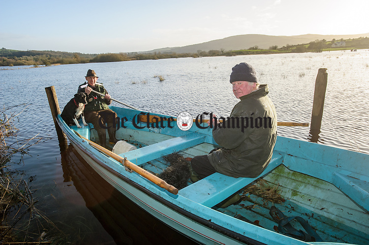 Doorus neighbours Gerard Mulqueen and James Peppard arrive safely across the flood waters by boat. A number of homes at Doorus, O Callaghan's Mills were cut off during the recent heavy rainfall which came with storm Desmond. Photograph by John Kelly.