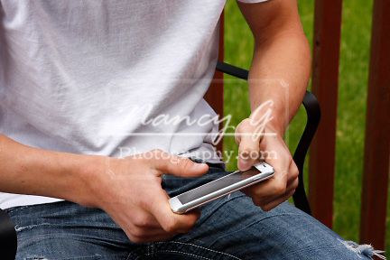 A teen boy using his smart phone outside on a deck