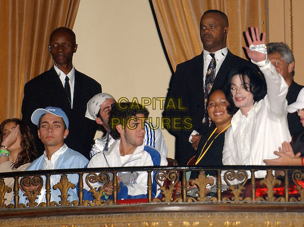 MICHAEL JACKSON & OMAR BHATTI.Singer Michael Jackson & Alleged son Omar Bhatti (blue baseball cap) at The MJ birthday party that was given by his fanclub at the Orpheum Theatre in Downtown L.A. California, USA, .August 30th 2003.half length balcony dead died blue cap hat white shirt wig hair 45th hand waving glove .CAP/DVS.©Debbie VanStory/Capital Pictures
