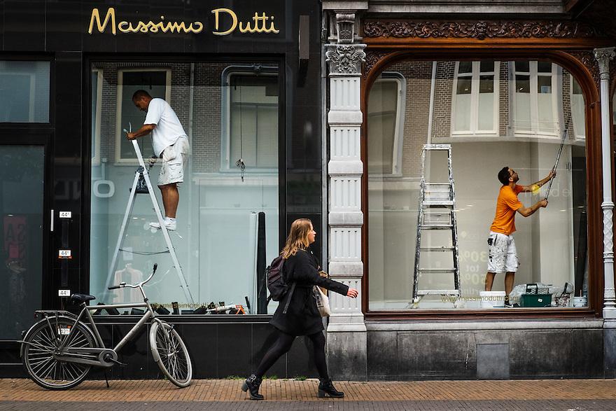 Nederland, Utrecht, 16 juni 2015 <br /> Vrouw loopt langs twee etalages waar geen producten geshowed worden maar waar wordt geschilderd. Schilders zijn bezig, trapleer staat tegen etalageglas. <br /> <br />  Foto: Michiel Wijnbergh