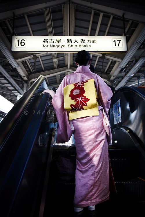 Tokyo, October 17 2011 - A Japanese woman wearing traditional Kimono about to board on the Shinkansen (Japanese bullet train) at Tokyo station.