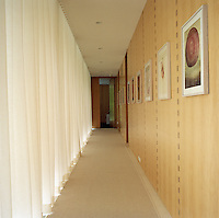 A sequence of paintings by Darren Waterston line the maple wall of the main corridor