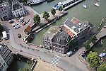 Looking down from overhead to cobbled street with cyclists, buildings and traffic, Dordrecht, Netherlands