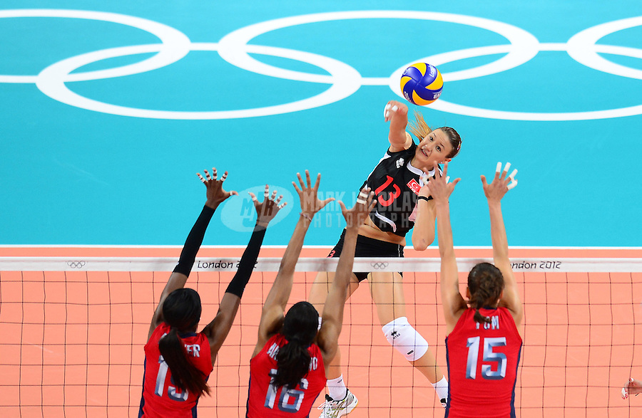 Aug 5, 2012; London , United Kingdom; Turkey player Neriman Ozsoy (13) hits the ball under pressure from USA defenders during the London 2012 Olympic Games at Earls Court. USA defeated Turkey in straight sets. Mandatory Credit: Mark J. Rebilas-USA TODAY Sports