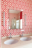 Detail of a double basin in a bathroom alcove papered with red and cream geometric wallpaper