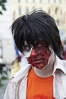 participant at the prague zombi walk in may 2014. Wearing an orange t-shirt with a white shirt over, and having open scars made in the face.