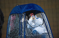 NWA Democrat-Gazette/CHARLIE KAIJO Bentonville fans protect themselves from the rain, Friday, November 29, 2019 during the Class 7A semifinal at Bentonville High School in Bentonville.