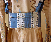 A detail of the blue and white striped sash with hand-painted polka dots. Gold ribbons also run from the waistline down the skirt of the garment