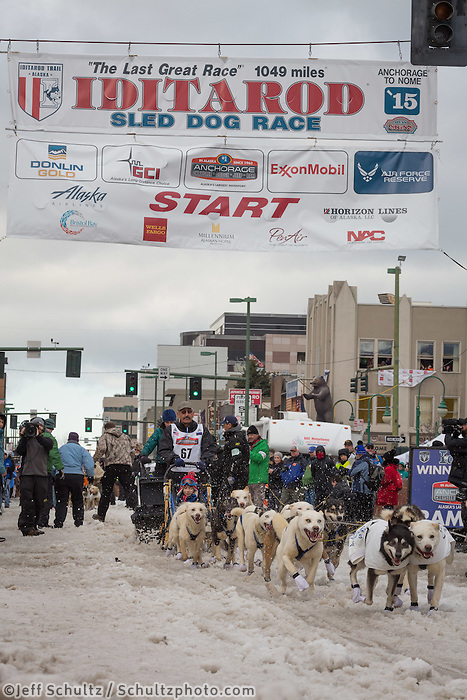 Chuck Schaeffer and team leave the ceremonial start line with an Iditarider at 4th Avenue and D street in downtown Anchorage, Alaska during the 2015 Iditarod race. Photo by Jim Kohl/IditarodPhotos.com