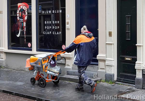 Nederland  Amsterdam -  2018.   Postbezorger op de Zeedijk.    Foto Berlinda van Dam / Hollandse Hoogte