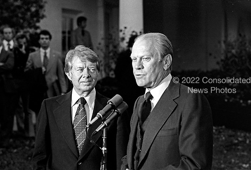 """United States President Gerald R. Ford, right, and US President-elect Jimmy Carter, left, meet reporters outside the Oval Office of the White House in Washington, D.C. following their discussions on the transition on November 22, 1976.  This is the first meeting between the two men since the Presidential debates during the campaign.<br /> Credit: Benjamin E. """"Gene"""" Forte / CNP"""