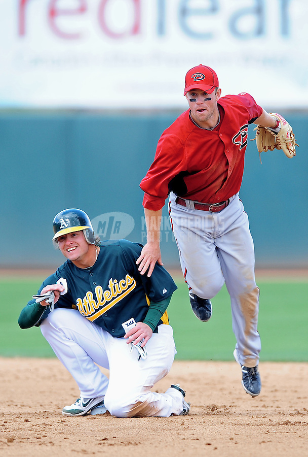 Mar. 19, 2012; Phoenix, AZ, USA; Arizona Diamondbacks second baseman Aaron Hill (right) throws to first base to complete the double play after forcing out Oakland Athletics base runner Josh Donaldson in the fourth inning during a spring training game at Phoenix Municipal Stadium.  Mandatory Credit: Mark J. Rebilas-
