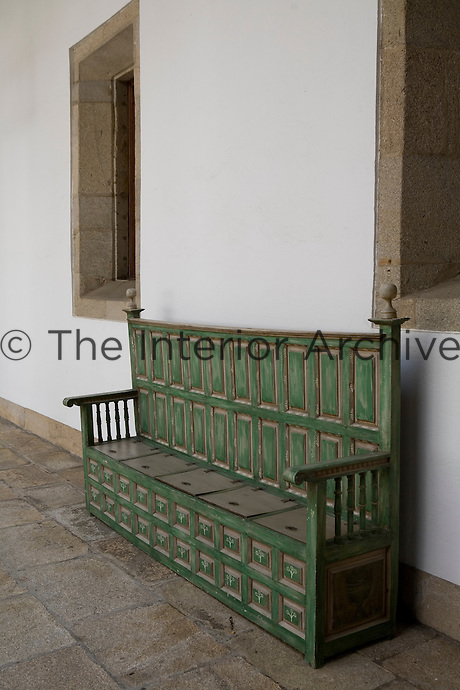 A monastic green bench seat in a courtyard at the Parador hotel, Hostal dos Reis Catolicos