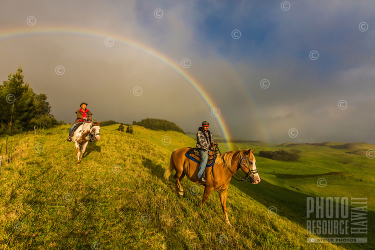 A horseback riding guide taking a young woman on a ride in beautiful Kohala are framed by a double rainbow, Hawai'i Island.