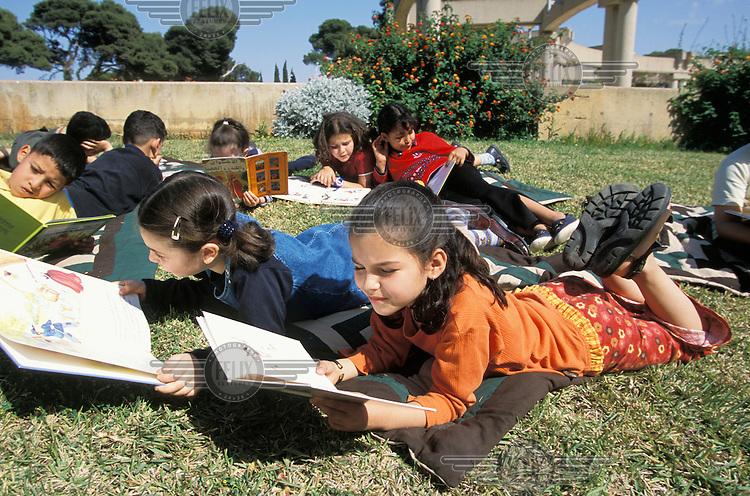 Primary school children reading books.