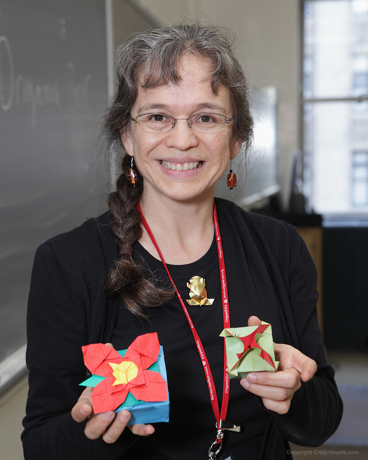New York, NY, USA - June 25, 2011: Leyla Torres at the OrigamiUSA convention holding two modular Origami models which she designed and is teaching to her class of students