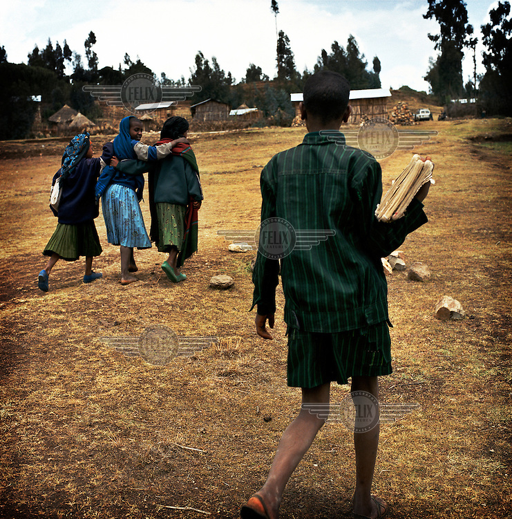 Girls huddle together as they walk to school, followed by a boy...