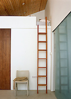 The extra ceiling space in this double-height room has been used to create a small bedroom accessed by a wooden ladder