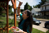 "Judy Nguyen applies stain to a gazebo during ""Circle the City with Service,"" the Kiwanis Circle K International's 2015 Large Scale Service Project, on Wednesday, June 24, 2015, in Indianapolis. (Photo by James Brosher)"