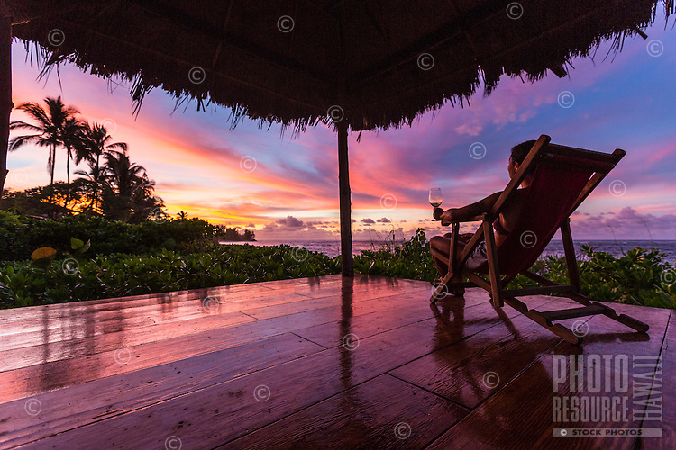 A woman enjoys a cocktail and a beautiful sunset from her beach gazebo along the North Shore of O'ahu.