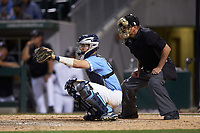 Home plate umpire David Savage stands behind North Carolina Tar Heels catcher Cody Roberts (11) during the game against the South Carolina Gamecocks at BB&T BallPark on April 3, 2018 in Charlotte, North Carolina. The Tar Heels defeated the Gamecocks 11-3. (Brian Westerholt/Four Seam Images)