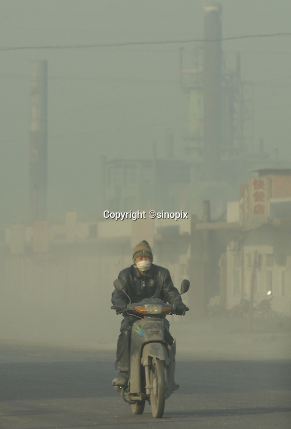 Locals cover their faces as they pass a coal power station and coking plant that spews carbon monoxide and sulphur dioxide in Linfen, Shanxi Province, China. Linfen has been identified as one of the most polluted cities in China..30 Jan 2007