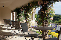 Outdoor seating on the covered terrace of the Hotel Endsleigh near Tavistock, Devon with a view to the gardens designed by Humphry Repton