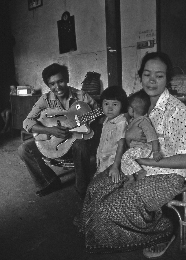 Family portrait in their home in Laos as father plays guitar