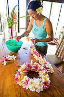 Local Asian woman making a plumeria lei