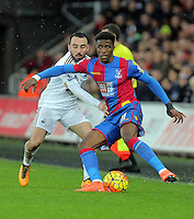 (L-R) Leon Britton of Swansea challenges Wilfried Zaha of Crystal Palace during the Barclays Premier League match between Swansea City and Crystal Palace at the Liberty Stadium, Swansea on February 06 2016