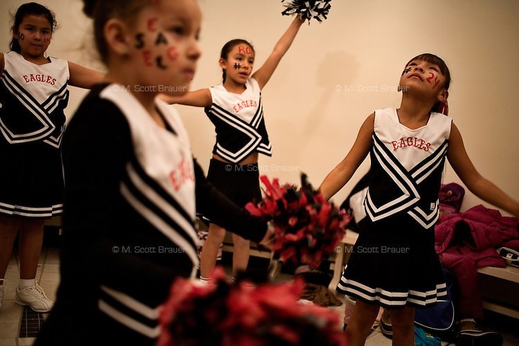 Cheerleaders from the White Clay Immersion School at Fort Belknap College prepare for a pep rally in support of the Fort Belknap College Eagles men's basketball team at Fort Belknap Agency, Montana, USA.  The cheerleaders are first graders in the school.  The White Clay Immersion School is a program aimed toward increasing fluency among younger generations in the White Clay language, the language of the Gros Ventre tribe.  The basketball team has helped raise money through its games to fund a breakfast program for the young students at the school.