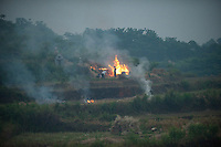 Daytime landscape view from a train of people tending to a fire on farmland near Wuhan in Hubei Province.  © LAN