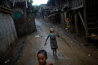 Myanmar's ethnic Karen children play as heavy rain hits their Mae La refugee camp outside Mae Sot near the Thai-Myanmar border October 14, 2010. Ethnic Karen refugees continue to pour into Thailand, fleeing decades long fighting between Karen rebels and Myanmar government troops and its guerrilla allies. Some 140,000 refugees live in official camps along the Thai-Myanmar border, according to the U.N. refugee agency and there are concerns that hostilities in the hills of Eastern Myanmar could intensify as a result of a refusal of several ethnic political groups to take part in an election next month.     REUTERS/Damir Sagolj (THAILAND)