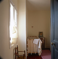 A view through an open doorway to a detail of a child's nursery room with cot in one corner