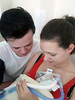 "COPY BY TOM BEDFORD<br /> Pictured: The premature baby held by parents Luc Protheroe and Paighton Waters at the Royal Gwent Hospital in Newport, Wales, UK <br /> Re: A young couple were granted their Christmas wish to cwtch their ""miracle"" baby for the first time.<br /> Little Flynn Protheroe was the same size as a mobile phone when he was born 14 weeks early.<br /> The tiny baby and his mother Paighton Waters, 19, were both given a 50-50 chance of surviving after a rare placental abruption.<br /> Flynn was born by Caesarian and doctors worked on him for 20 minutes to get his tiny heart and lungs working.<br /> Meanwhile Paighton was on the critical list after losing four litres of blood.<br /> But five weeks later the pair are doing well and have been allowed to hold their little boy for a Christmas cuddle.<br /> Proud dad Luc Protheroe, 21, said: ""It's a miracle, I could have lost them both."